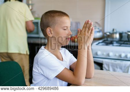 Caucasian Boy Prays At Home At Table Before Eating. Stay Home And Pray To God. Online Church Worship