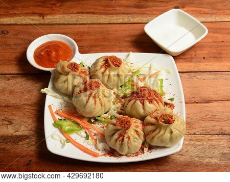 Veg Steam Momo.topped With Peri Peri Masala And Served With Sauce And Mayonnaise Over A Rustic Woode