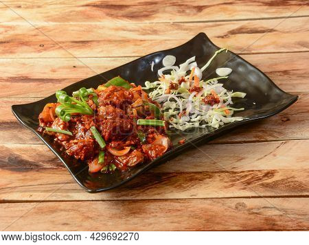 Mutton Chilli Or Lamb Chilli, Spicy And Delicious Dish Served Over A Rustic Wooden Background, Selec