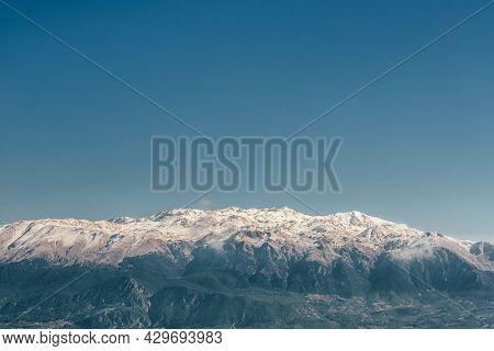 Snowy mountain range against the deep blue sky. Mountain peaks with the blue sky on the background.