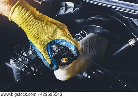 The Mechanic Is Open Or Close The Car's Brake Fluid Reservoir Cap To Check The Brake Fluid Level