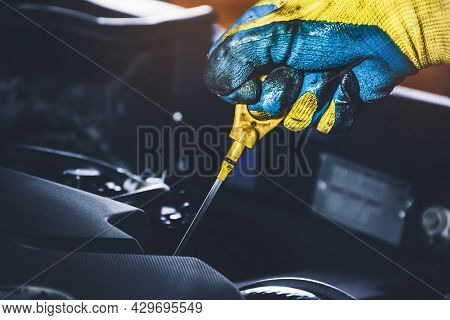 Technician Hand Pulling Oil Dipstick For Checking Lubricating Oil Level Of The Car Engine