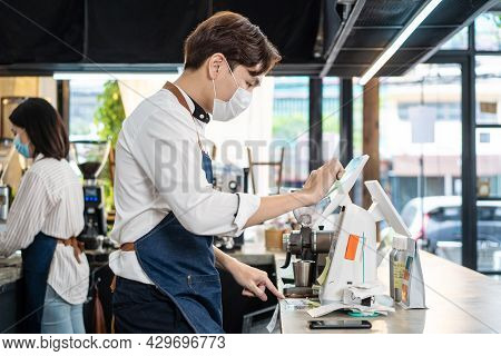Asian Cafe Shop Owner Man Check Sale Order From Laptop On Counter Bar. Young Restaurant Waiter Wear