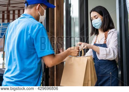 Asian Food Deliverly Man Wear Protective Mask Due To Covid-19 Pandemic, Show Online Order On Phone T