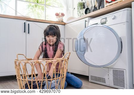Asian Young Little Kid Put Dirty Clothes Into Washing Machine In House. Lovely Girl Child Sit On Flo