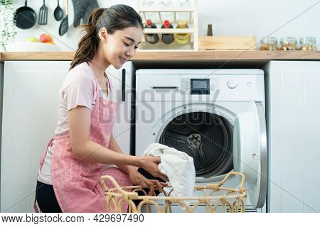 Asian Beautiful Woman Put Dirty Clothes To Washing Machine In House. Attractive Girl Wear Apron Sit