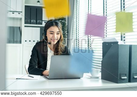 Asian Business Female Call Center In Formal Wear Working In Workplace. Attractive Beautiful Professi