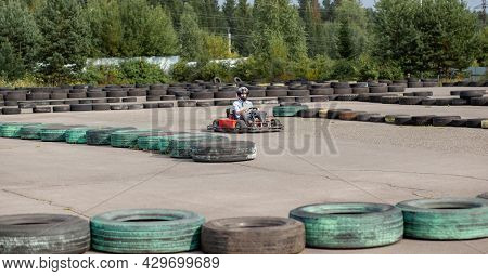 A Girl Or A Woman In A Hard Hat Rides A Go-kart On A Special Track Fenced With Rubber Wheels. Active