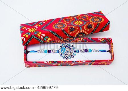 Beautiful Blue Diamond Design Rakhi And Gift Box Over White Background.raksha Bandhan Festival Is Ce