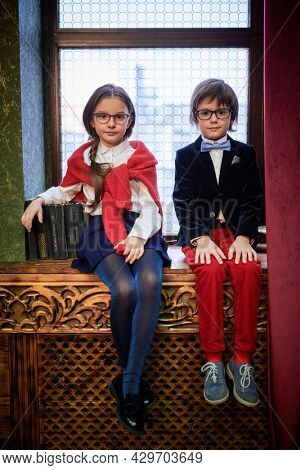 Two cute modern kids in elegant classic school uniform and glasses are sitting on the windowsill in a luxurious vintage interior. Christmas decoration. Kid's school fashion.