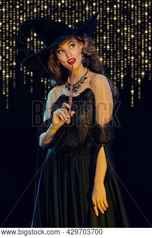 Portrait of an enchanting young woman witch with  with a magic wand on background with shiny golden lights. Halloween party, make-up and costume. Magic on Halloween.