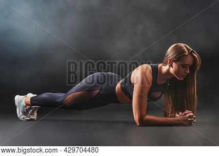Full length portrait  of a beautiful sportive brown-haired young woman in black clothes doing a plank on black smoky background. Studio fashion shot.