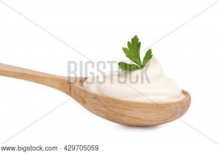 Delicious Sour Cream With Parsley In Wooden Spoon On White Background
