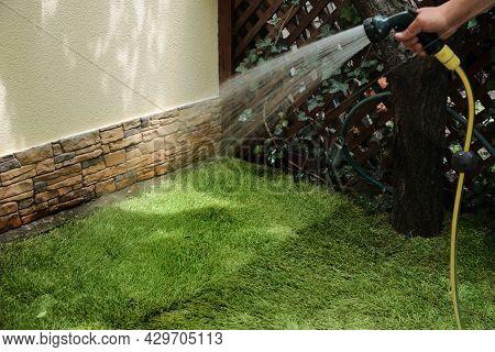 Man Watering Unrolled Grass Sods At Backyard, Closeup