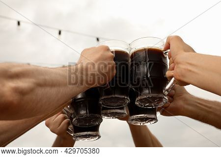 Friends Clinking Glasses With Beer In Outdoor Cafe, Closeup