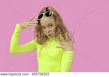 A Beautiful Cheerful Girl In Sunglasses On A Colored Background.