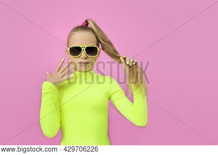 A Beautiful Girl In Sunglasses On A Colored Background.