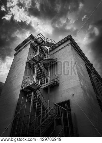 A City Building With A Fire Escape On The Background Of The Sky With Clouds.