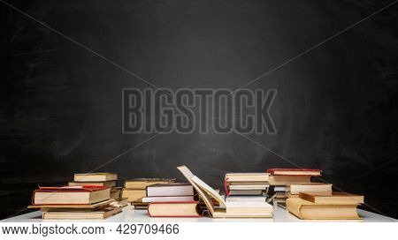 Education concept - Books on the desk with the background of the blackboard