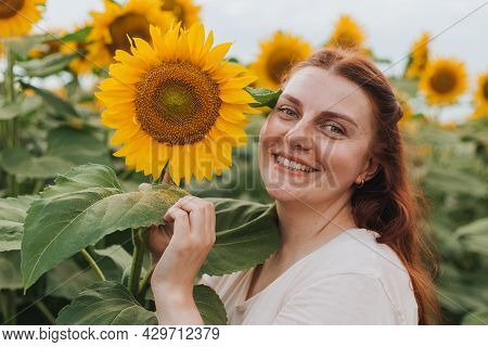 Happy Smiling Female Standing In Sunflowers Field On Summer Day. Harvest Time. Summer Vacation