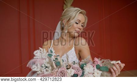 Close-up - A Bride In A White Dress Holds A Wedding Bouquet In Her Hands, Showing Flowers To The Cam
