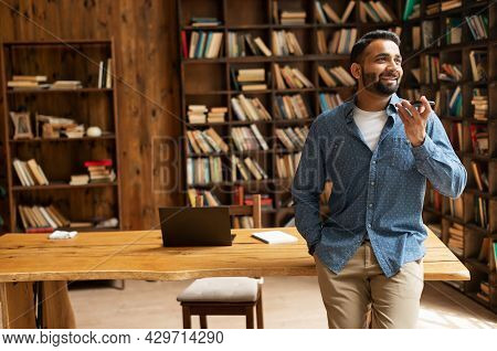 Cheerful Indian Man Using Convert Voice Into Text Mobile App, Holding Smartphone, Talking Into A Mic