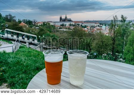 Traditional Czech Draft Lager Beer And White Wine In Plastic Cups,blurred Prague Castle And Petrin F
