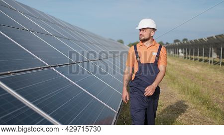 Male Engineer In Uniform Walking And Looking At Solar Power Plant. Man In Hard Helmet Examining Obje