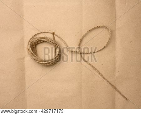 Brown Folded Twine On A Brown Paper Background, Rope For Household Needs, Top View