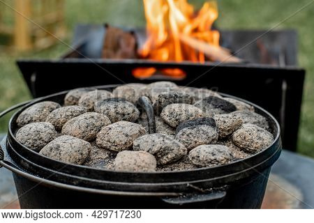 Dutch Oven Camp Cooking With Coal Briquettes Beads On Top. Campfire Camping Life