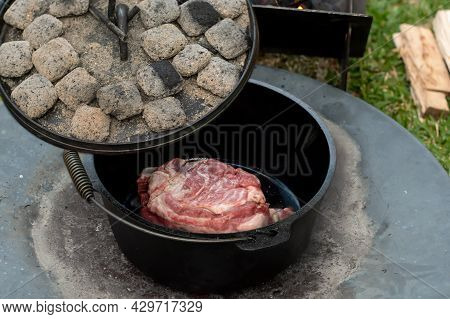 Dutch Oven Camp Cooking With Coal Briquettes Beads On Top, Meat Lamb Shoudler In The Camp Oven. Camp