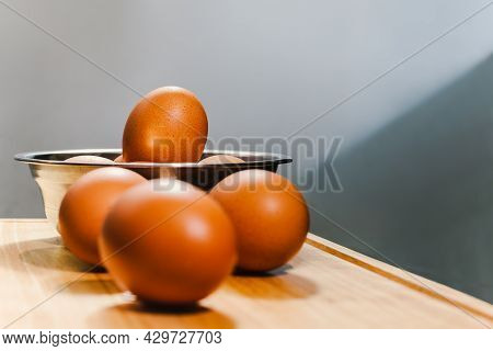 Brown Chicken Eggs In Silver Bowl On Wooden Board