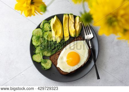 Delicious Breakfast With Avocado, Fresh Cucumbers And Microgreens Of Peas With Dill, Fried Eggs On B