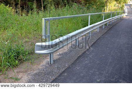 Path For Cyclists With An Asphalt Surface. Galvanized Iron Railing Over Road Barriers. Bridge Railin