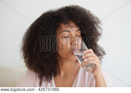 Close-up Shot Of A Black Woman Drinking Still Water. Hydrate Desire, Maintain Water Balance