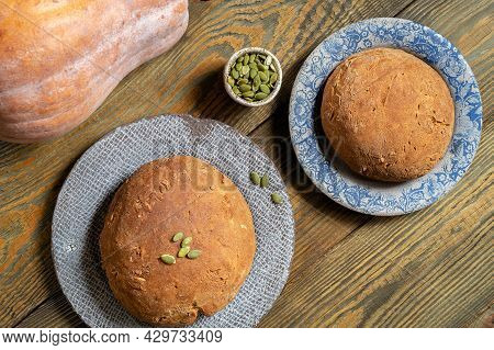 Two Rolls Of Bread With Seeds Are Lying On Ceramic Plates, Next To A Fresh Pumpkin. Home-made Yeast-