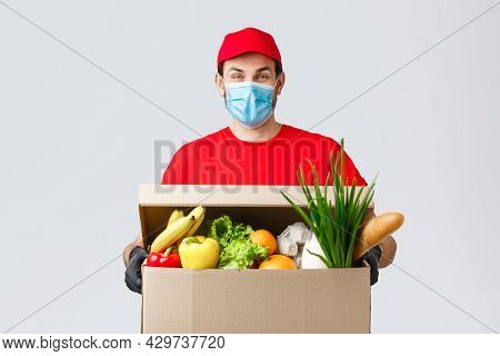 Groceries And Packages Delivery, Covid-19, Quarantine And Shopping Concept. Friendly Courier In Face