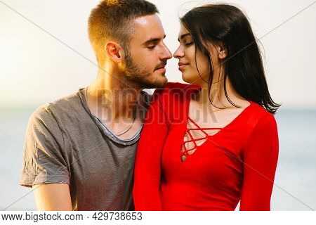 Beautiful Young Couple In Love, The Man Looking At His Pretty Girlfriend In Red Sexy Dress With Love