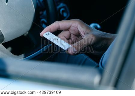 closeup of a young man, in a casual wear, looking to a covid-19 antigen diagnostic test device, waiting for the results, while is sitting in the driver seat of his car
