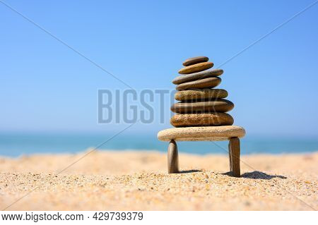 A Pebble Tower Stands On The Seashore On Two Thin Stones. Equilibrium Figure Of Sea Pebbles Against
