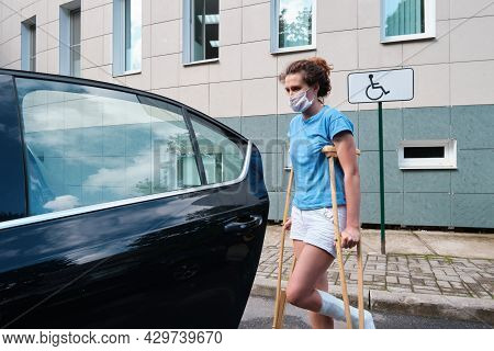 A Woman With An Injured Leg Gets Into A Car. Orthopedic Plaster, Orthopedic Crutches. Limited Mobili