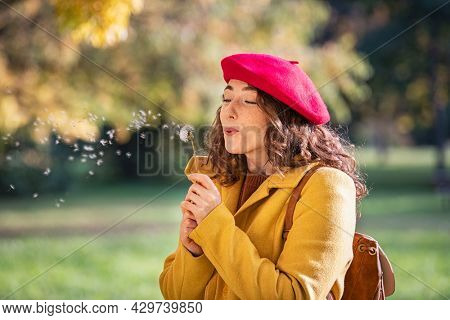 Beautiful young woman blowing dandelion while standing in autumn park. Portrait of a carefree girl in meadow holding dandelion in hand. Playful woman relaxing at park.