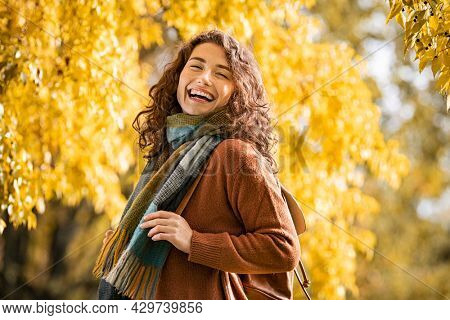 Carefree young woman wearing scarf with a big grin on face at park during autumn season. Smiling casual girl with warm and winter clothes enjoying sunny day at park with yellow trees on background.