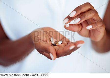 Close up hands of mature african woman taking beauty supplements for glowing skin. Black mid woman adding pills to heap of medicines. Middle aged female hands with bunch of medicines for healthy skin.