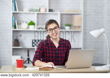 Beautiful Asian Woman Relaxing Using Laptop Computer While Sitting On Table. Creative Girl Working A