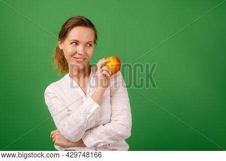 A Good-looking Woman Of Forty In A White Shirt On A Green Background Smiles And Holds A Fresh Apple