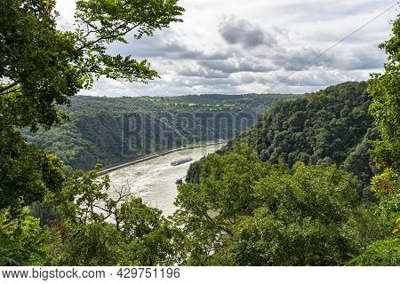 The River Rhine In Western Germany Flows Between The Hills Covered With Forest, Visible Barge And Wo