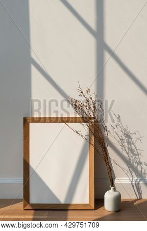 Dried white statice flower in a white vase by an empty wooden frame on a wooden floor