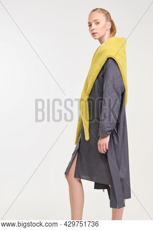 Beautiful fashion model poses in stylish dark grey dress and yellow fur scarf from the spring-summer collection. Full length studio portrait on a white background. Haute couture clothing.