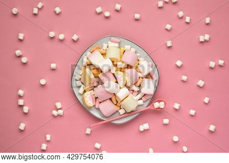 Colorful Marshmallows On A White Square Plate Isolated On A Pink Background. Scattered Marshmallows.